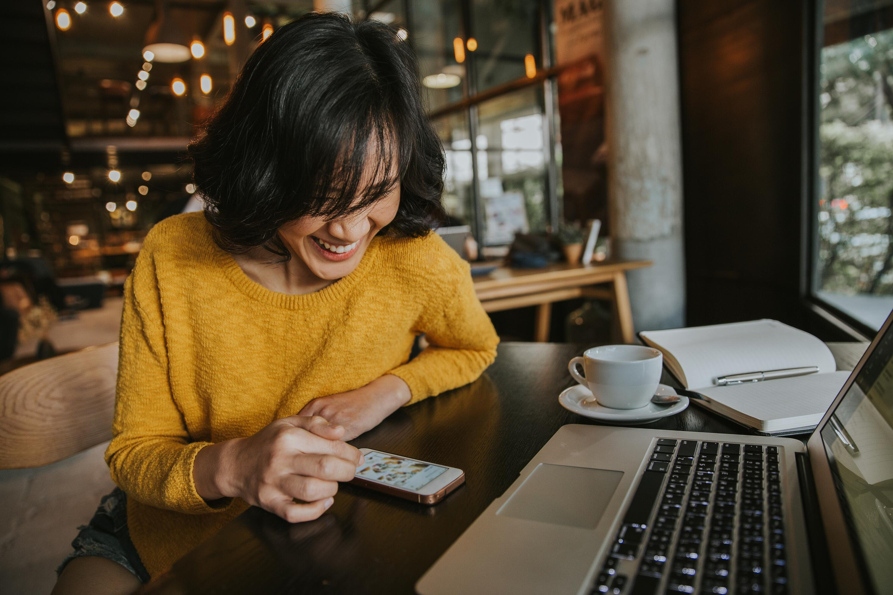 young-hipster-woman-smiling-sitting-in-coffee-shop-using-smartphone-smiling-technology-happy-internet_t20_XznLE6